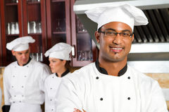 Indian chef. A happy indian young chef with his european colleagues in background Royalty Free Stock Photo