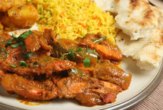 Indian Chicken Curry Meal. Indian chicken jalfrezi with Bombay aloo, pilau rice and naan bread Royalty Free Stock Image