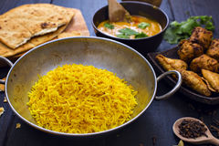 Indian chicken pilau rice in balti dish served with tikka masala. Indian pilau rice in balti dish served with chicken tikka masala curry, plain naan bread Stock Image