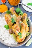 Indian chicken tandoori, marinated in greek yogurt  and spices, served with lime wedges, cilantro and basmati rice, vertical,  top stock photography