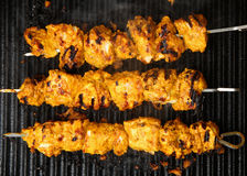 Indian Chicken Tikka Kebabs on Griddle. Indian tandoori chicken tikka kebabs, marinated in yoghurt and spices, cooking on griddle plate Royalty Free Stock Image