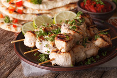 Indian chicken tikka on skewers close-up and naan. Horizontal. Indian chicken tikka kebabs on skewers close-up on a plate and naan. Horizontal Royalty Free Stock Images