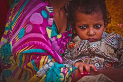 Indian child on hands of his mother Stock Photos