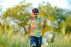Indian child playing with the color in holi festival stock photo