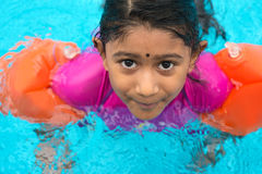Indian child swimming. Indian child learning swimming in pool. Asian girl in swimmer class with float bands Royalty Free Stock Photo