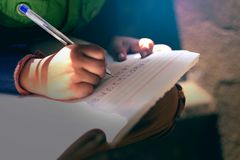 Indian child writing on note book. Writing hand Stock Photo