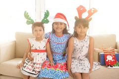Indian children and Christmas gifts. Happy Indian family celebrating Christmas holidays, with gift box and santa hat sitting on sofa or couch at home, adorable stock photos