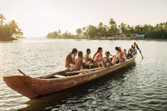 Indian children get to school by boat. Kochi, India - January, 5, 2016:Old Indian man transporting children to school across the river on a wooden boat in Kerala Stock Photography