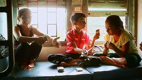 Indian Children Play Cards Laugh in Moving Train Carriage. VARKALA, KERALA/ - NOVEMBER 20 2012: Closeup Indian children squat on table play cards laugh in moving stock video footage