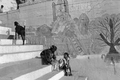 Indian Children playing with kit. Two Indian girls are playing with a kit on the stairs of Benaras in front of a wall painting Royalty Free Stock Photography