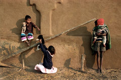 Indian children playing with kits. Two young Indian rural children are playing with kits while another young boy is looking after a little kid on his lap Royalty Free Stock Photography