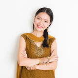 Indian Chinese girl in sari. Portrait of arms crossed mixed race Indian Chinese woman in traditional Punjabi dress smiling, standing on plain white background Stock Images
