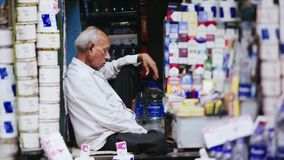 Indian city. Koikata, India - December 2016, tilt-shift view through people crowd, life on indian street, portrait eldery man siting in our small tobacco shop stock footage