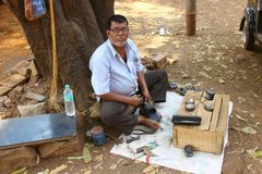 DAPOLI, MAHARASHTRA, INDIA, February 2018, Indina Cobbler works at his shop at Khed, Kokan. Indian cobbler with his street shop at Khed, Dapoli, Kokan royalty free stock photo