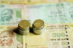 Indian coins stack with currency notes in background Royalty Free Stock Photos