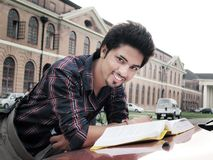 Indian college student reading book. Indian / Asian college student studying in campus Stock Photo