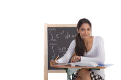 Indian college student woman studying math exam. High school or college ethnic Indian female student sitting by the desk at math class. Blackboard with advanced Royalty Free Stock Photo