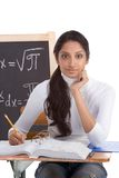 Indian college student woman studying math exam. High school or college ethnic Indian female student sitting by the desk at math class. Blackboard with advanced Royalty Free Stock Photography