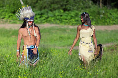 Indian couple. Indian chief with a young Indian go on the green meadow Royalty Free Stock Photos