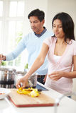 Indian Couple Cooking Meal At Home Stock Photos