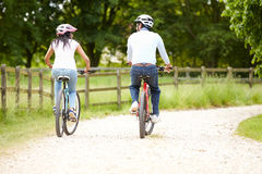 Indian Couple On Cycle Ride In Countryside. Cycling Away From Camera Into Distance Royalty Free Stock Photos