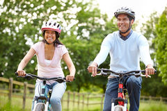 Indian Couple On Cycle Ride In Countryside. Looking Into Distance Smiling Whilst Wearing Helmets Stock Photography