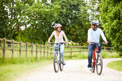 Indian Couple On Cycle Ride In Countryside. Wearing Helmets Smiling At Each Other Stock Photography