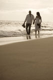 Indian couple holding hands walking on a beach together. Happy Indian couple holding hands walking on a beach together in the surf Royalty Free Stock Image