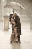Indian couple kissing under an umbrella in the rain ki Royalty Free Stock Photos