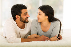 Indian couple lying bed. Cheerful indian couple lying on bed Stock Photo