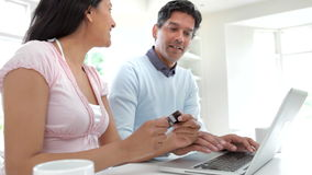 Indian Couple Making Online Purchase At Home. Asian Indian couple sitting at kitchen counter with laptop, entering credit card details for exciting purchase and stock video