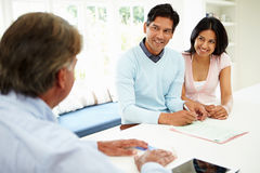 Indian Couple Meeting With Financial Advisor At Home. Signing Documents Stock Photography