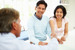 Indian Couple Meeting With Financial Advisor At Home. Sitting Down Shaking Hands Stock Images