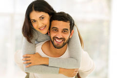 Indian couple piggyback. Happy young indian couple having fun with piggyback indoors Stock Image