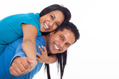 Indian couple piggyback. Happy young indian couple having fun with piggyback on white background Stock Photo