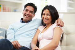 Indian Couple Sitting On Sofa Watching TV Together. With Arm Over Shoulder Stock Photos