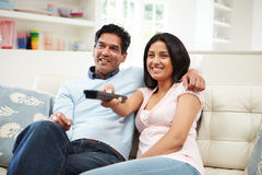 Indian Couple Sitting On Sofa Watching TV Together. Pointing Remote Control Royalty Free Stock Photos