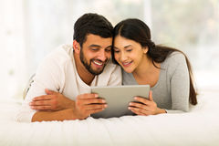 Indian couple tablet pc. Happy young indian couple lying on bed and using tablet pc at home Stock Image