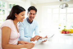 Indian Couple Using Digital Tablet At Home. Sitting At Table In Kitchen Stock Photography