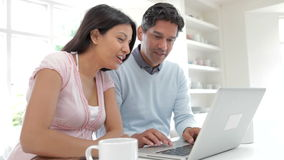 Indian Couple Using Laptop Computer In Kitchen At Home Royalty Free Stock Photos