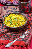 Indian cuisine: bowl of yellow rice with green peas Stock Photo