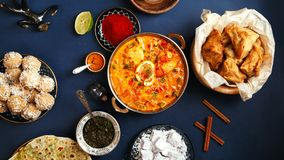 Indian cuisine on diwali holiday. Tikka masala, samosa, patties and sweets with mint chutney and spices. Dark blue background. Banner composition