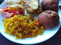 Indian food rice, bread, potato, vegetables. Goa, India. Indian cuisine food on plate - spicy rice, potato, vegetables, bread in Goa, India stock image