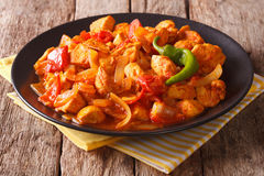 Indian Cuisine: Spicy chicken jalfrezi with pepper and onion clo. Se-up on a plate. horizontal Stock Photography