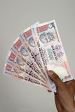 Indian currency. Close up of a  hand with indian currency  thousand rupee notes Stock Photos