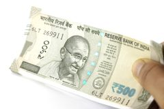 A Bundle of Indian Rupees in hand. Indian currency, five hundred rupees notes bundle held in hand. Giving Money Stock Images