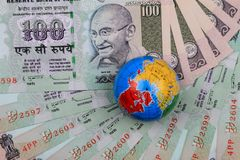 Indian Currency Rupees with a Globe royalty free stock photography