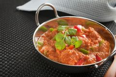 Indian Curry Chicken Jalfrezi. Popular Indian curry Chicken Jalfrezi, chicken stir fried with spices, with a tomato sauce and red and green capsicums, in a balti Stock Photo