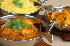 Indian Curry Dishes. Chicken dansak with Bombay aloo vegetable curry and pilau rice Stock Image