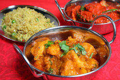 Indian Curry Food Meal Dinner. Close-up of Bombay Aloo curry dish with chicken curry and special pilau rice Royalty Free Stock Photo